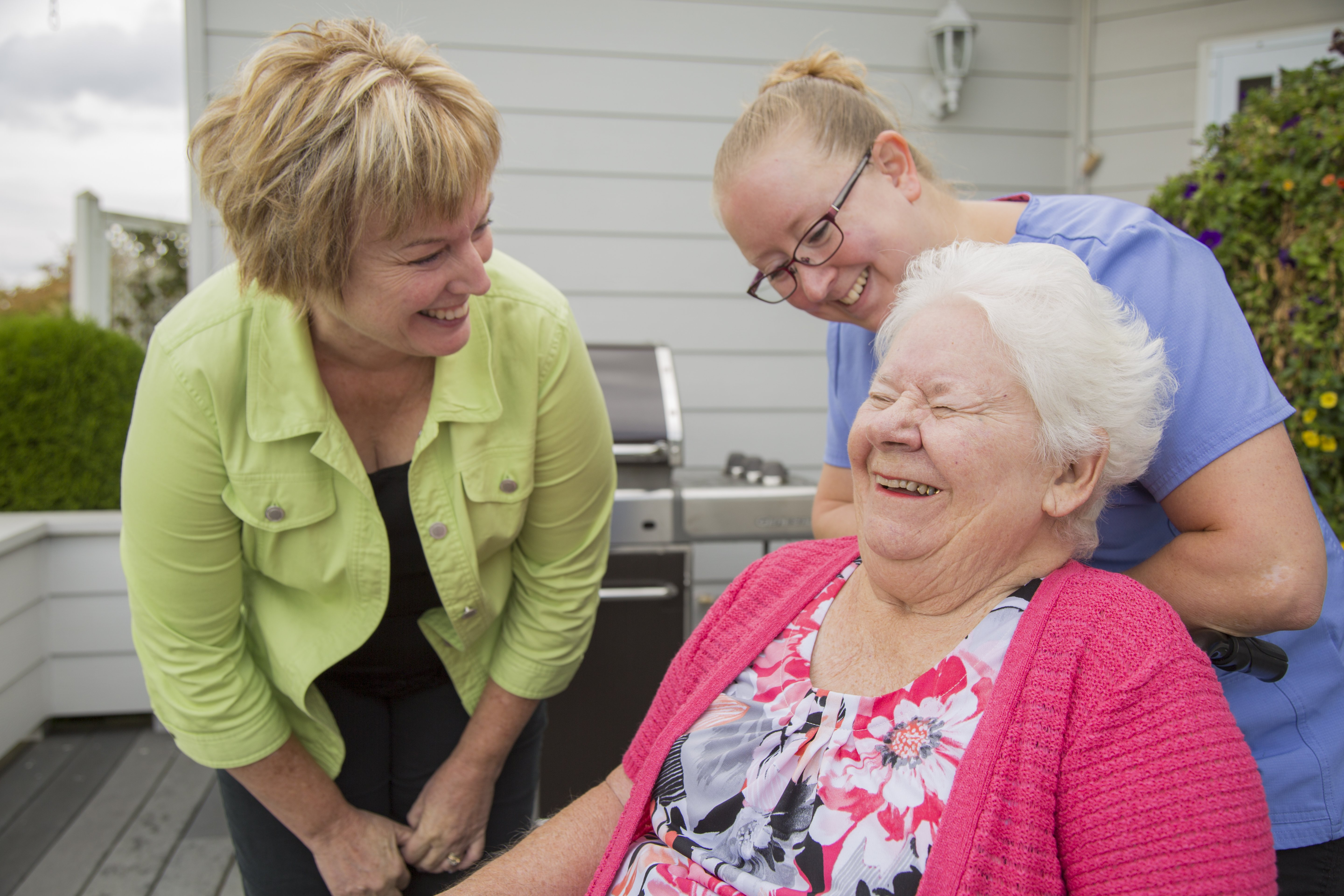 Two caregivers laugh with an elderly client outdoors on a patio.