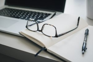A writing notebook lies open next to a silver laptop. A pair of reading glasses and a pen sit on the open notebook.