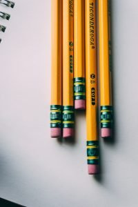 Five yellow Ticonderoga No. 2 pencils are arrayed next to each other on a notebook.