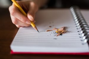 A hand holds a pencil and prepares to write. Pencil shavings are strewn across the notebook paper.