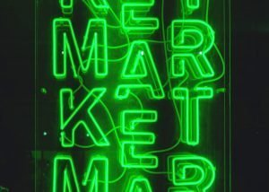 "A green neon sign spells out the work ""MARKET"""