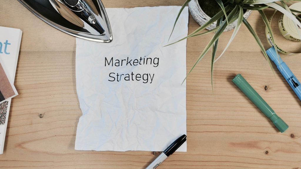 "A white piece of paper lying on a cluttered desk bears the words ""marketing strategy."""
