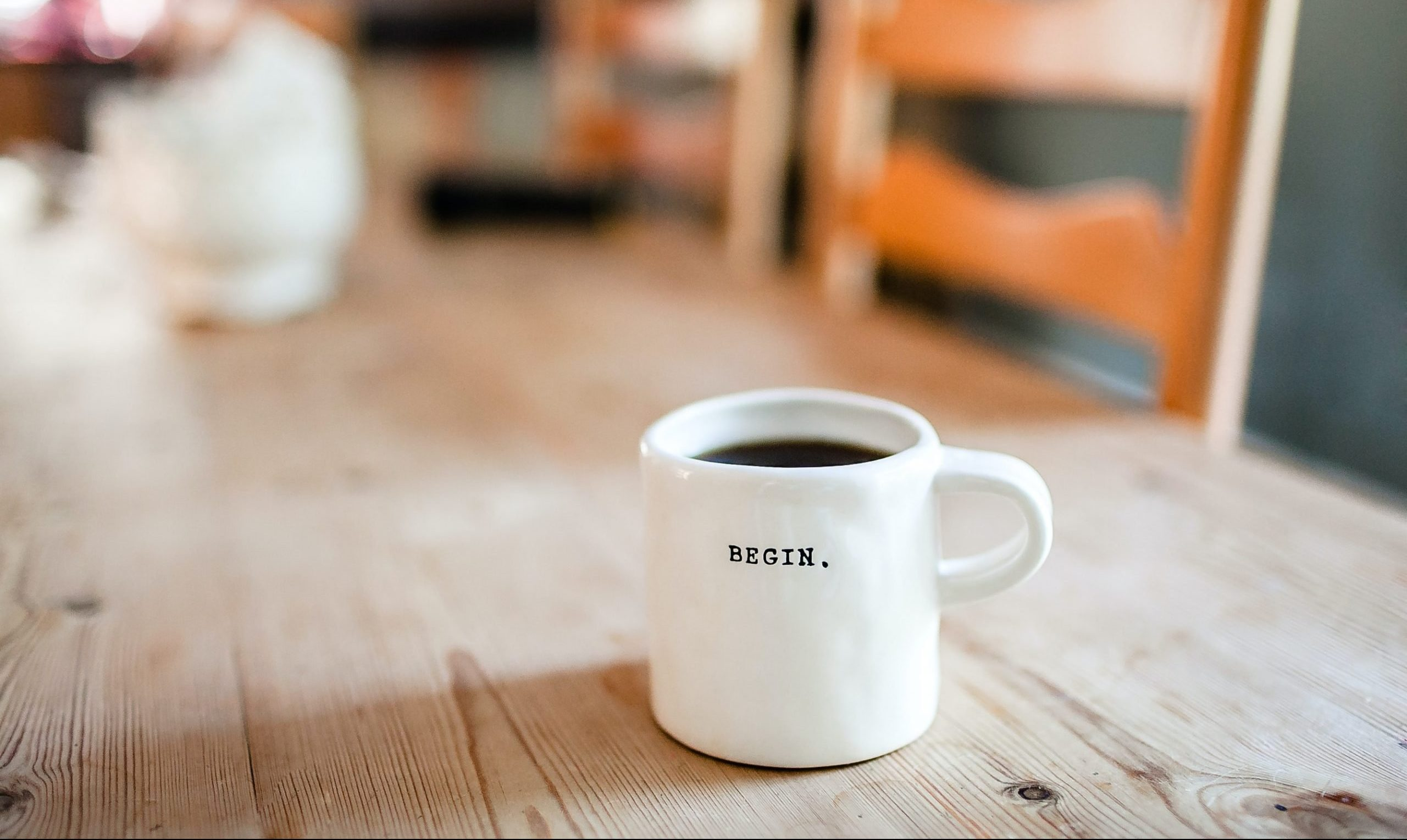 "Coffee mug stamped with the word ""begin"" resting on a wooden table."