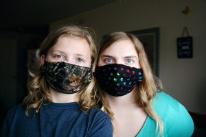 A mother and daughter look into the camera, both wearing face masks.